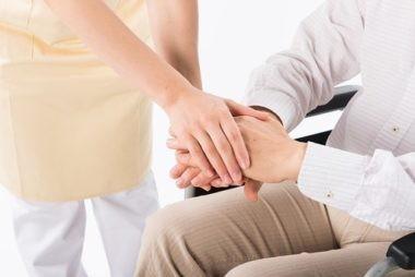 手を握る車椅子の人